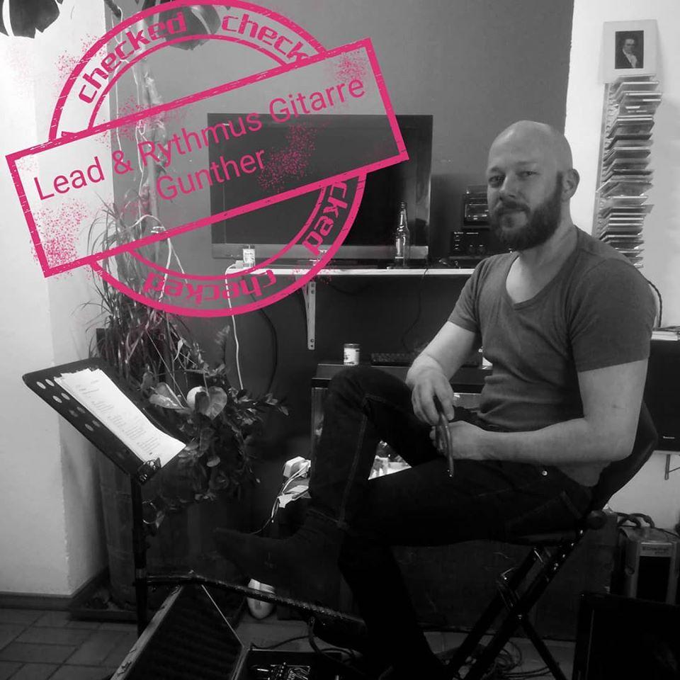 Gunther Eisler sitzt entspannt bei der Probe und hat eine Brezel in der rechten Hand